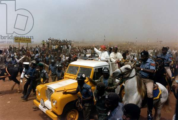 Pope John Paul II greets Christian believers, onboard a jeep