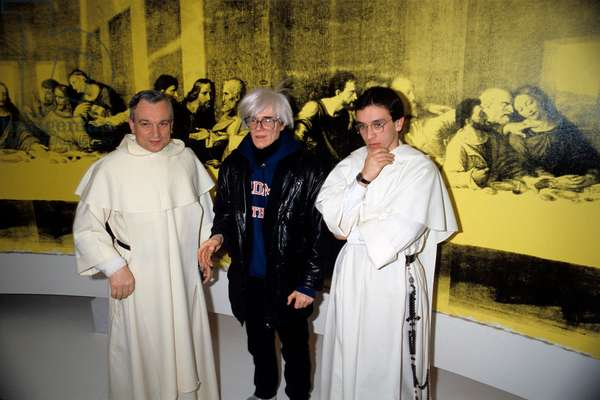 American artist Andy Warhol (Andrew Warhola Jr. ) posing with two dominican fathers in front of his painting The Last Supper inspired by Leonardo's fresco. Milan, January 1987, Palazzo delle Stelline