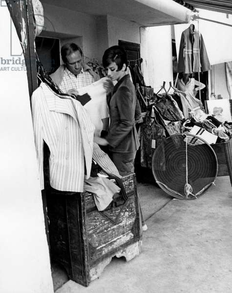 Mel Ferrer with his wife Audrey Hepburn is trying a sweater, 1966 (b/w photo)