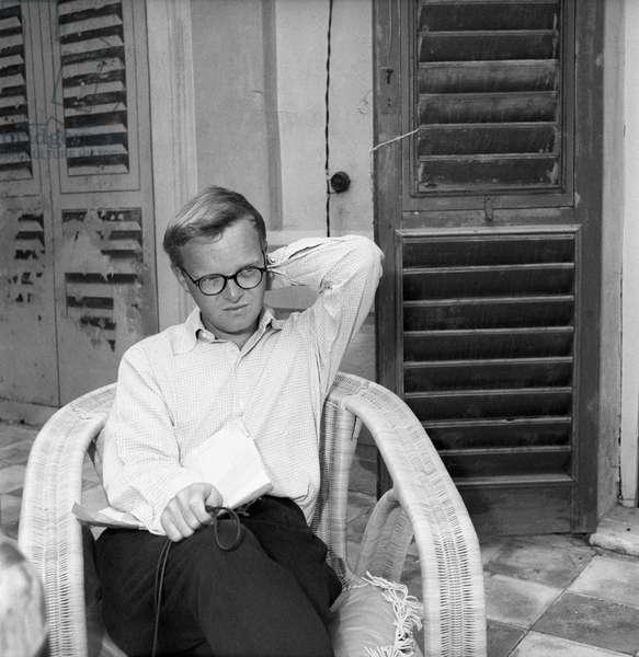 Truman Capote sitting on a wicker chair, Portofino, Italy