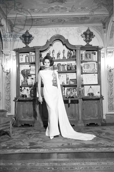 Sophia Loren posing in her home in front of a book shelf, 1964 (photo)