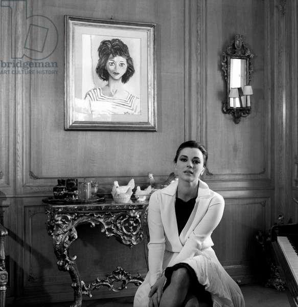 Giovanna Ralli sitting near a portrait made by Guttuso
