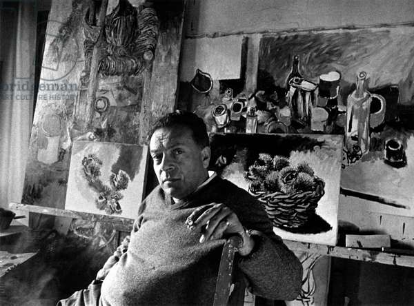 Renato Guttuso seated among his paintings
