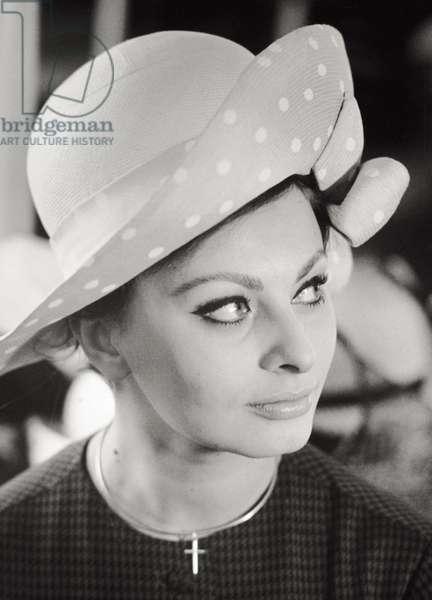 Sophia Loren is trying on a hat in a shop 'Berthet', 1963 (b/w photo)