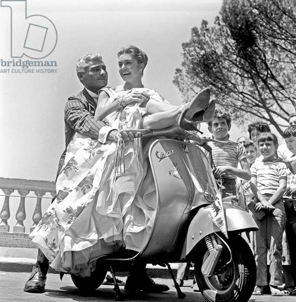 Jeff Chandler and Esther Williams posing on a Vespa, Rome, Italy, 1958 (b/w photo)