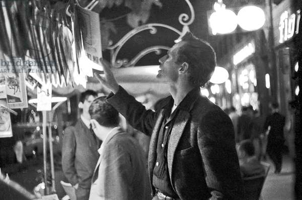 Charlton Heston watching the magazines at the kiosk, Rome, Italy, 1958 (b/w photo)