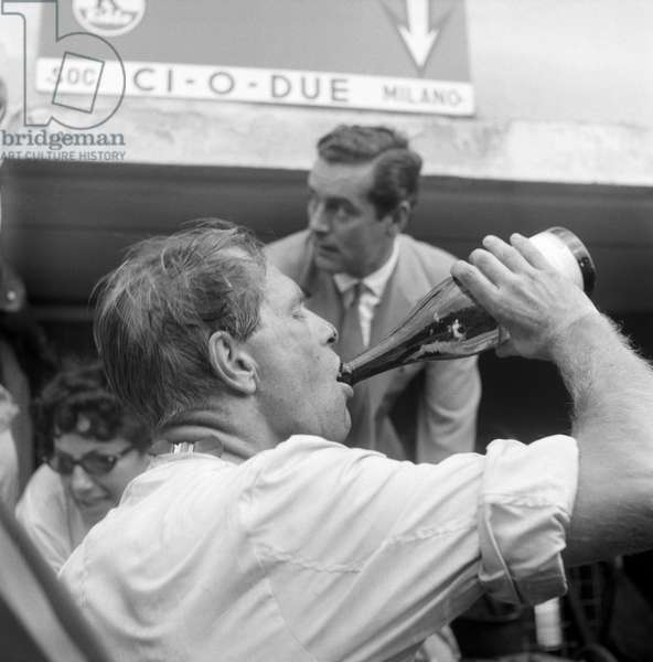 A man drinking something in the Autodrome at Italian Grand Prix, Monza, Italy, 2nd September 1956 (b/w photo)