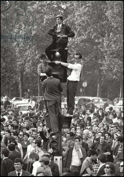 During a demonstration of Gaullists, who poured into the Champs Elysees after the decision of the President of the French Republic Charles de Gaulle to dissolve the National Assembly, by supporting the trade unions and the democratic institutions, four men climb to the top of a traffic light to watch the march and take some photos. Paris (France), May 30, 1968 (b/w photo)