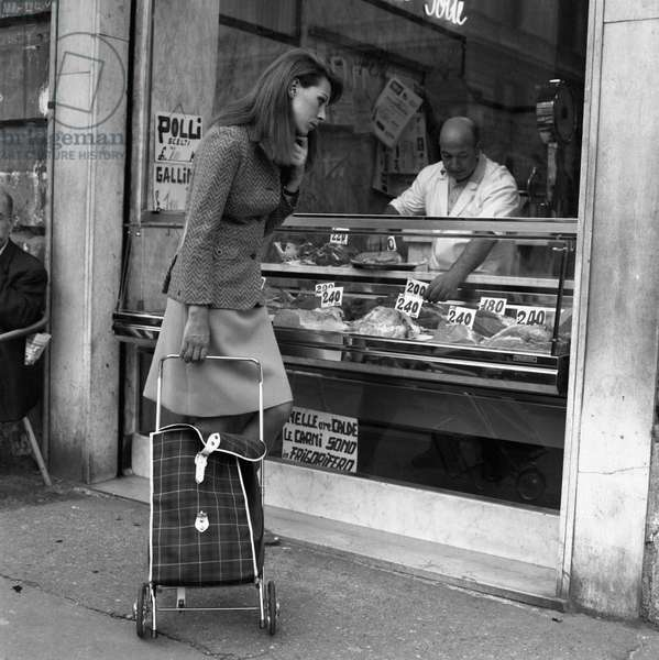 A woman watching the prices of the meat, Italy