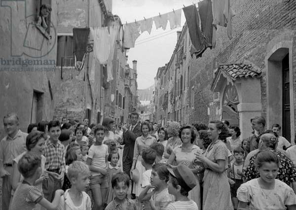 Yves Montand, Francoise Arnoul and Anouk Aimée surrounded by fans, Italy, 1955 (b/w photo)