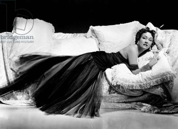 Gloria Swanson lying on a sumptuous sofa with a cocktail in her hand
