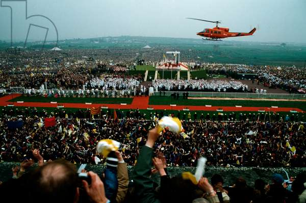 A crowd of Christian believers greeting the arrival of papal helicopter