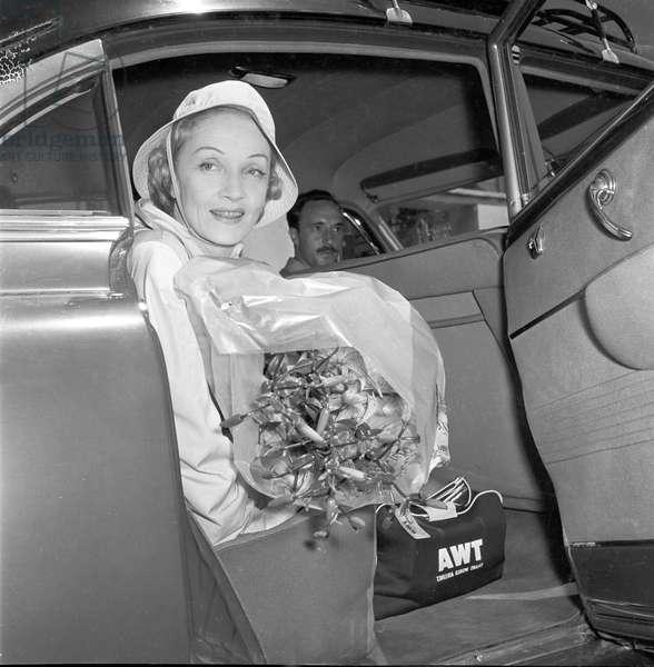 Marlene Dietrich getting into a car with a big bunch of flowers, 1957 (b/w photo)