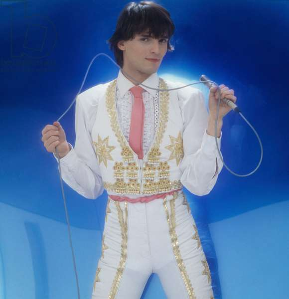 Miguel Bosé holding a microphone in a torero costume, Italy