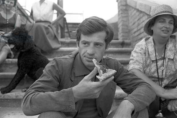 Jean Paul Belmondo eating a pizza, Italy, 1960 (b/w photo)