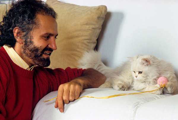 Gianni Versace plays with a cat throwing it a ball of wall