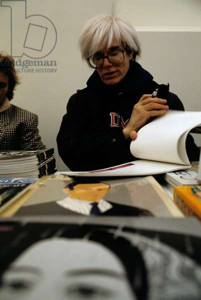 Andy Warhol signing some copies of the catalogue