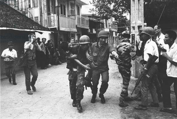Vietnamese soldiers are carrying an injured person