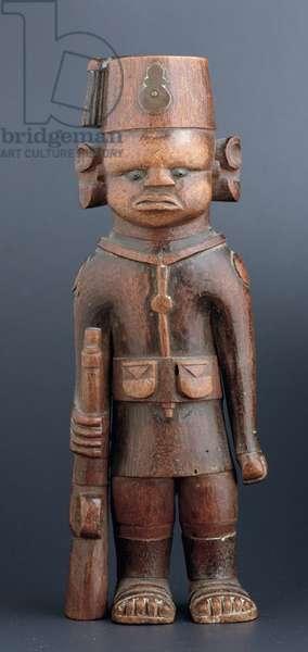 An Askari figure wearing a fez with a metal cap badge, Kamba, Kenya, first half 20th century (wood)