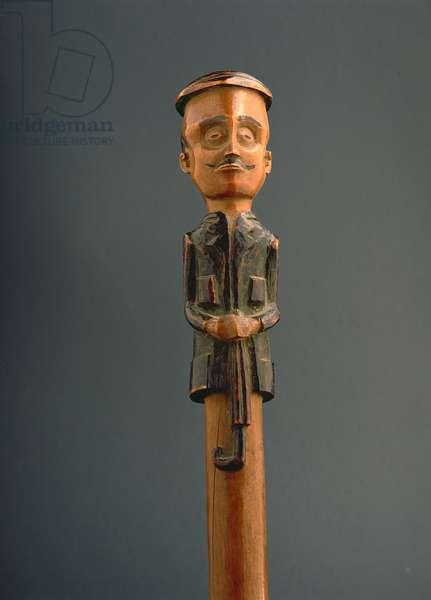 Stick with a figure of a European man wearing a cap and holding an umbrella, Ovimbundu, Angola, late 19th century (wood)