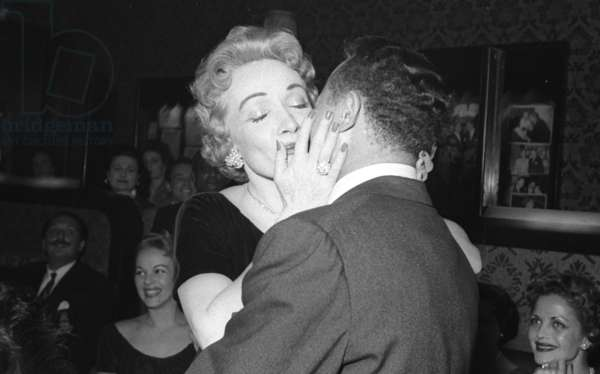 Marlene Dietrich kissing singer Billy Daniels, and her daughter, Maria Riva, in the background, Stork Room, London, UK, 1956 (b/w photo)