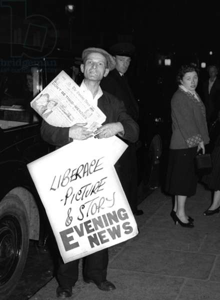 Max the newsboy with news-sheet advertising Liberace, Piccadilly Circus, London, UK, 1956 (b/w photo)