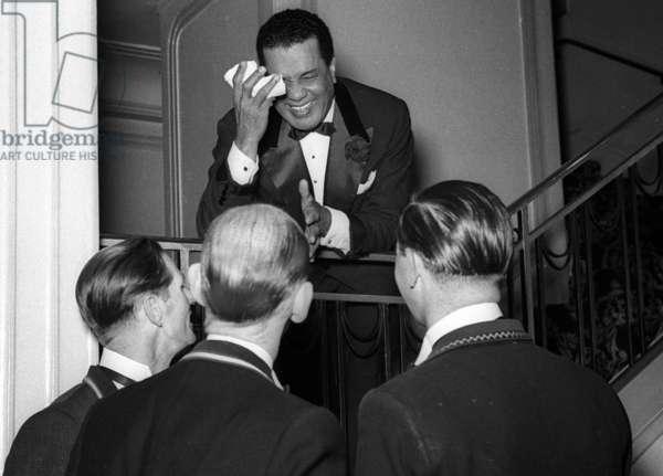 Lesley Hutchinson 'Hutch' entertaining the doormen at Quaglino's Restaurant, London, UK, 1956 (b/w photo)
