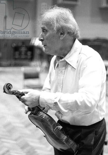 Yehudi Menuhin cleaning his violin, London, 1976  (b/w photo)