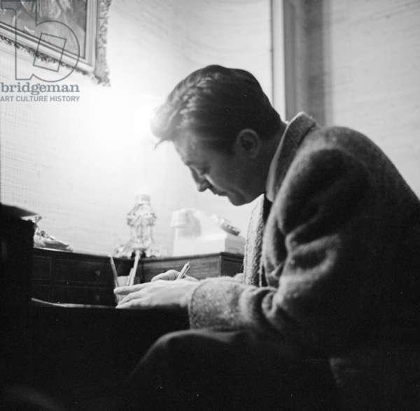 Robert Mitchum signing a fan photo, London, UK, 1960 (b/w photo)