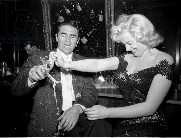 Sabrina's party trick with the actor Steve Cochran: a champagne glass crushed in her bare hand, Society Bar, London, UK, 1956 (b/w photo)