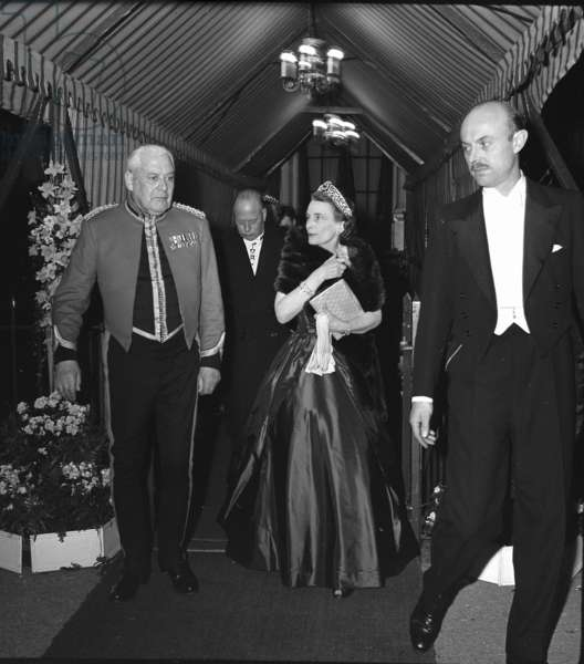 Duke and Duchess of Gloucester leaving a regimental dinner escorted by Brigadier Philip Bowden-Smith and Hotel Manager, Hyde Park Hotel, London, UK, 1958 (b/w photo)
