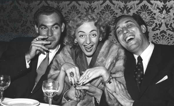 Christine Jorgensen with Norman Newell and Newell's partner, Stork Room, London, UK, 1954 (b/w photo)