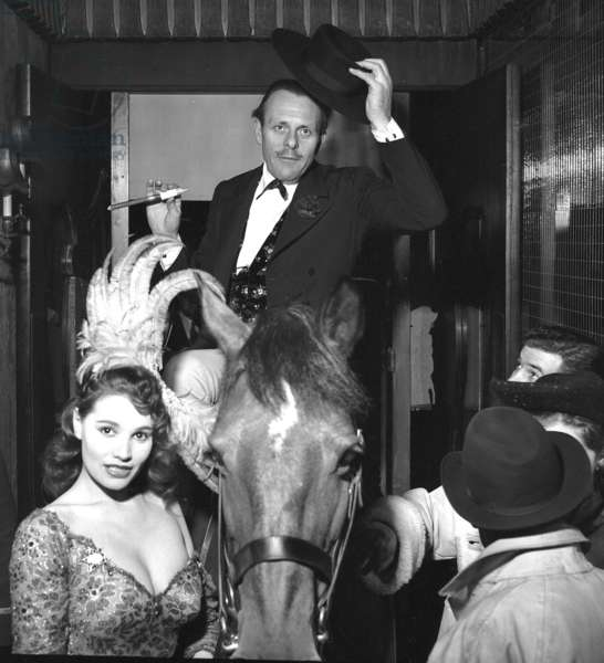 Actor Terry Thomas entering the Pigalle Theatre Restaurant on a horse and showgirl Yvonne Buckingham, London, UK, 1959 (b/w photo)