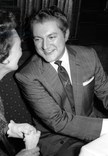 Liberace playing with a journalist, Society Bar, London, UK, 1956 (b/w photo)