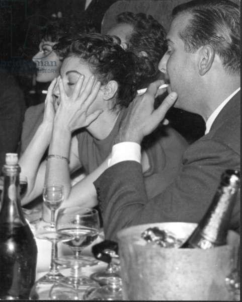 Ava Gardner and friend, Stork Room, London, UK, 1957 (b/w photo)