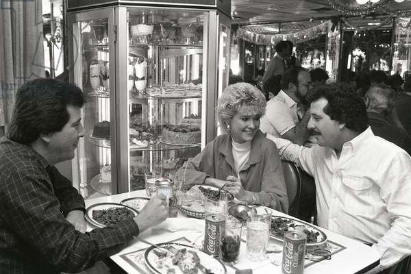 Enjoying Cuban cuisine at Versailles Restaurant, 1987 (b/w photo)