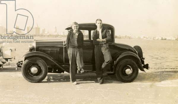 The young Hutton boys stand proudly in front of their car at the edge of Biscayne Bay, the City of Miami behind them, 1937 (b/w photo)