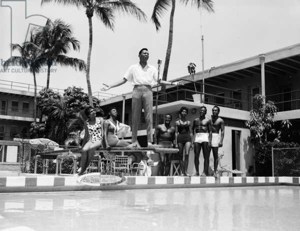 A singer entertains guests, poolside at the Sir John Hotel, May 11, 1962 (b/w photo)