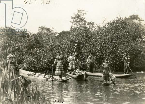 Seminole children and a woman ride along in canoes on a waterway in the Everglades, c.1920 (b/w photo)