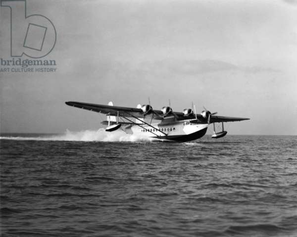A Pan Am seaplane skims the water, c.1936 (b/w photo)