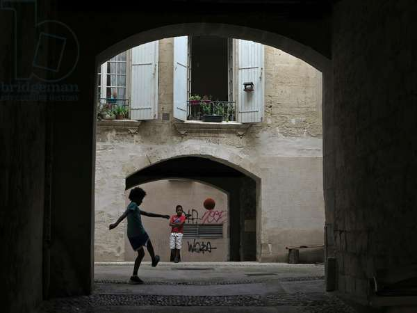 Arles, France, 2013. Children playing football in a street