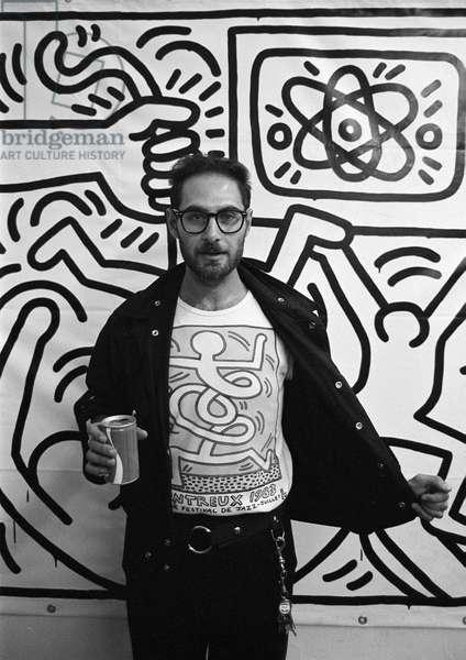 Italian journalist Roberto D'Agostino wearing a Keith Haring t-shirt in front of a Keith Haring painting (about 1980)/Il giornalista Roberto D'Agostino con una maglietta di Keith Harig davanti a un quadro di Keith Haring (1980 circa) -