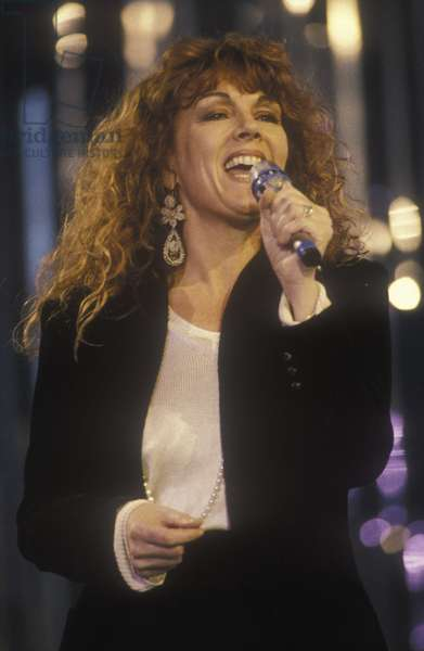 "Sanremo Music Festival 1990. Italian pop singer and record producer Caterina Caselli sings """" Bisognerebbe non pensare che a te"""" (coupled to the English version sung by Miriam Makeba: """" Give me a Reason"")/Festival di Sanremo 1990. Caterina Caselli canta """" Bisognerebbe non pensare che a te"""" (abbinata alla versione inglese cantata da Miriam Makeba: """" Give me a Reason"""") -"