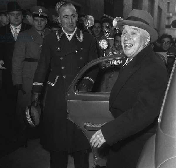 """Rome, 20-12-1952 Movie director and actor Charlie Chaplin gettinng out of a car to go in the """"Fiamma"""""""" movie theater/Roma, 20-12-1952 L'attore e regista Charlie Chaplin mentre scende da un 'automobile per entrare nel cinema """""""" Fiamma"""""""""""" - Marcello Mencarini Historical Archives"""