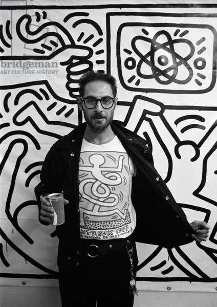 Italian journalist Roberto D'Agostino wearing a Keith Haring t-shirt in front of a Keith Haring painting (about 1980) (photo)