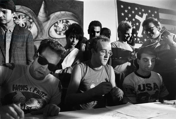 Milan, 1985. American artists Kenny Scharf, Keith Haring and Ronnie Cutrone during a press conference after a performance at the Fiorucci store/Milano, 1985. Gli artisti Kenny Scharf, Keith Haring and Ronnie Cutrone durante una conferenza stampa dopo una performance nel negozio Fiorucci -