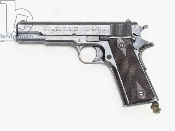 Colt 1911 A1 pistol. The stock has chequered walnut grips. The butt incorporates the magazine and there is a magazine release catch on the underside of the butt. The detachable box magazine takes seven rounds. The frame incorporates the trigger guard. The cocking slide takes up the whole of the top of the weapon. Semi-automatic, with recoil action. Rounds are thrust up into the breech by the magazine spring when the action is to the rear. After cocking for the first round, the weapon is automatically reloaded. The action is semi-automatic as the trigger has to be squeezed for each seperate shot. The barrel is rifled, for the most part enclosed within the slide. The barrel has a blade foresight and a notch rear sight. The calibre is 0.45in. Supplies of these pistols were shipped to Britain during 1915/16. Serial numbers special to this contract were prefixed by the letter W. ©National Maritime Museum, Greenwich/Leemage