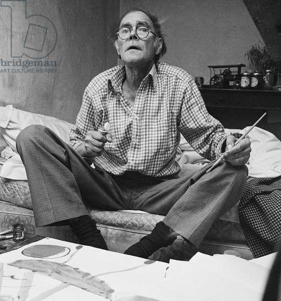Roger Hilton on bed, 1973 (b/w photo)