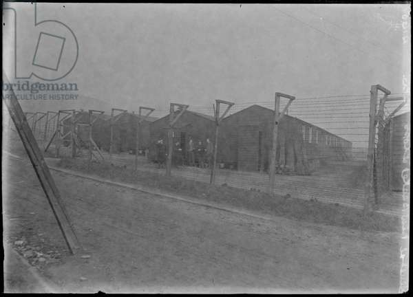 First World War Internees in front of an Internment Hut (barbed wire in foreground), Knockaloe Camp, Isle of Man, 1918 (b/w photo)