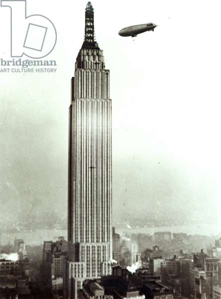 The Empire State Building in the course of construction with a US navy Airship J4 flying above it, December 16, 1930 (b/w photo)